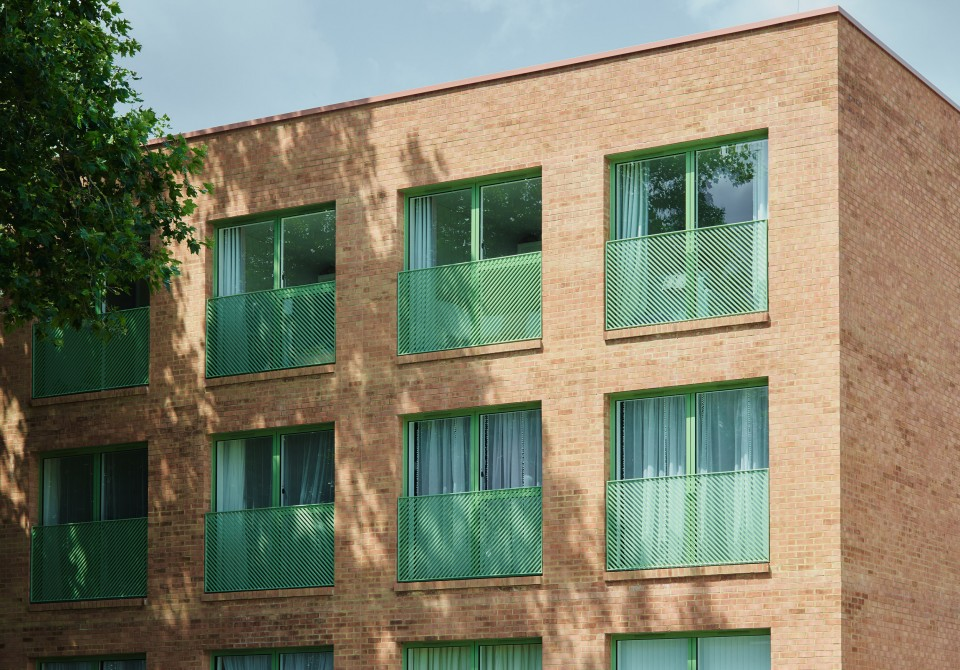 Brick building with green juliet balconies and a tree